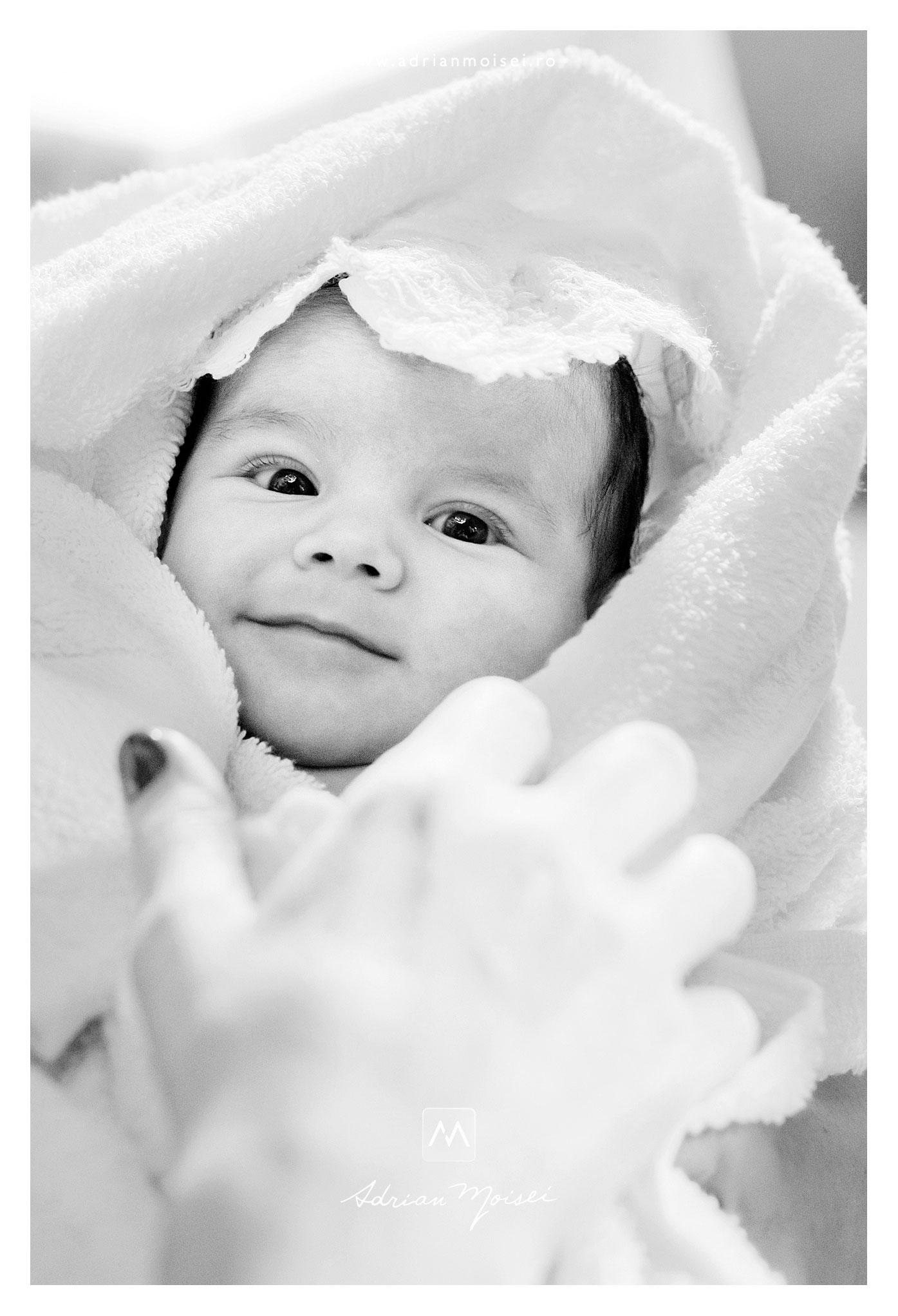 Portret de nou-născut, privind spre camera relaxat și zâmbitor, după slujba de botez, la Iași. Fotografie alb negru realizată de Adrian Moisei - fotograf Iași