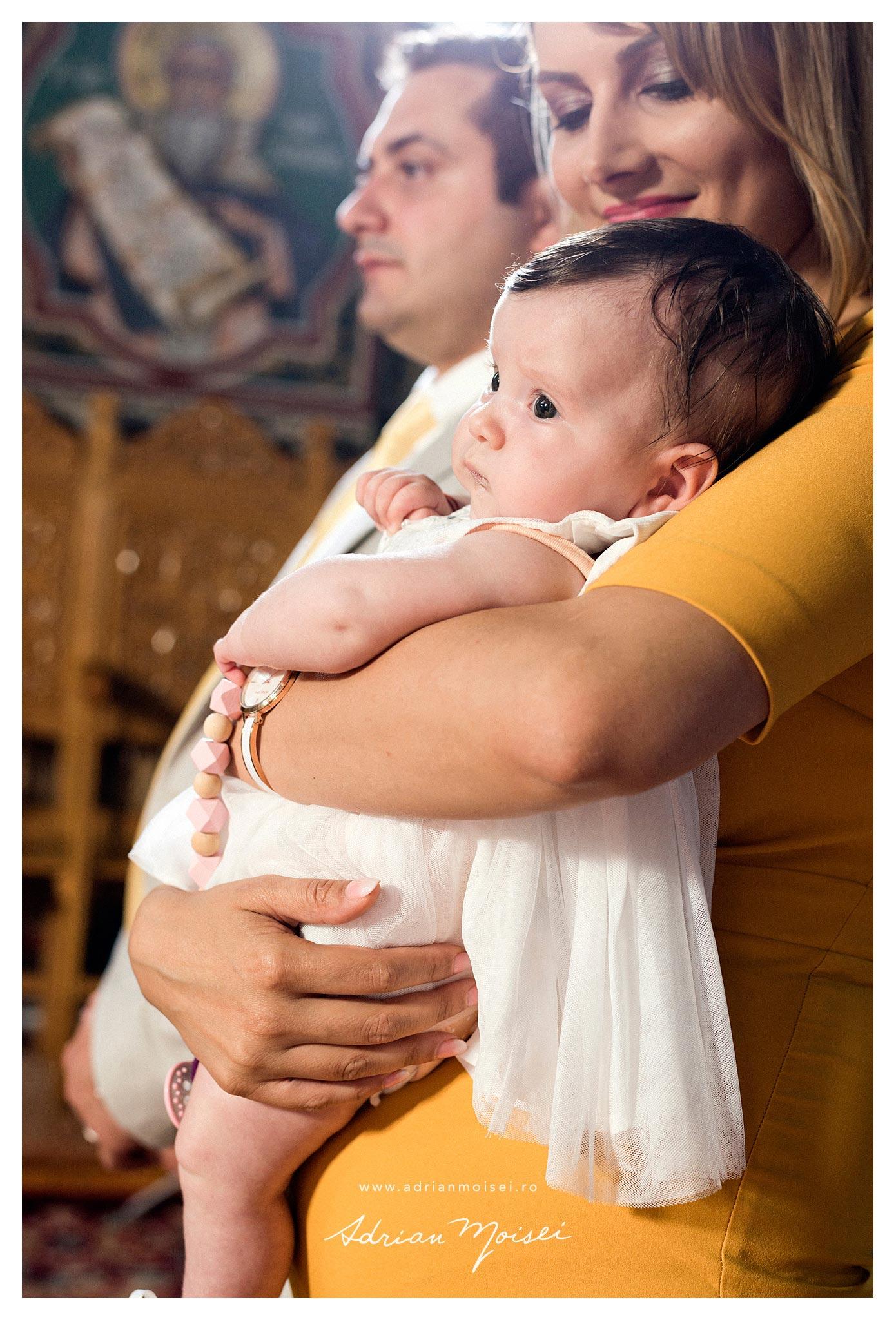 Portret de bebelus in bratele nanei, la botez, fotografie de Adrian Moisei