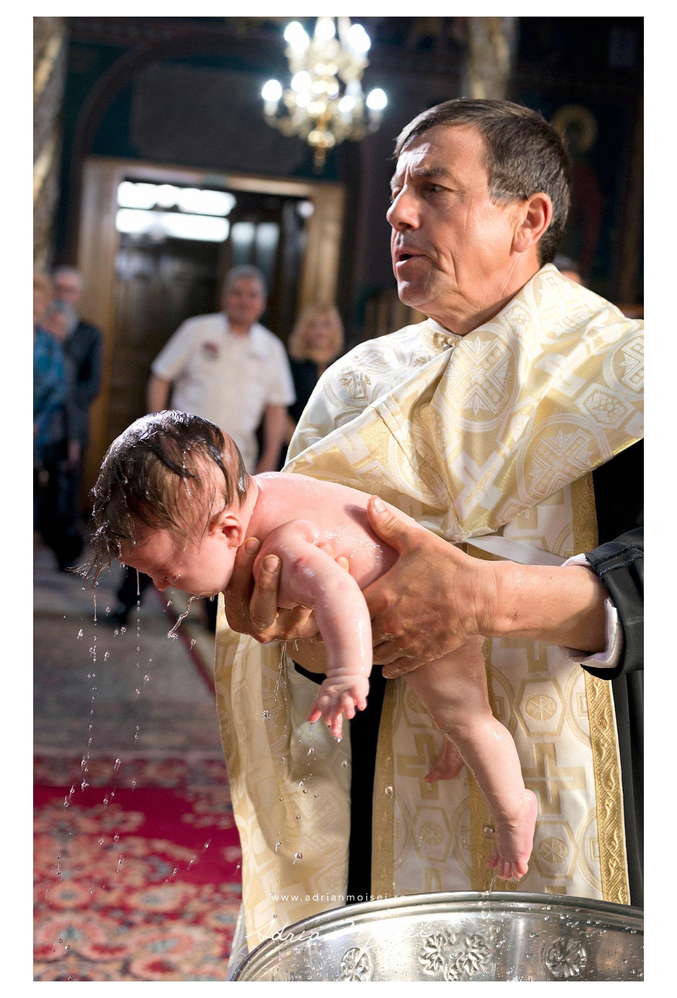 Fotografie de botez, bebelus in bratele preotului care il scoate din cristelnita, Adrian Moisei