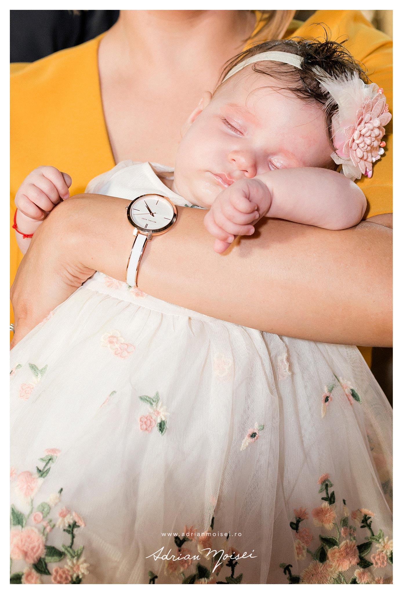 Bebelus dupa botez, dormind in bratele mamei, fotografie de Adrian Moisei